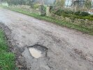 Large pothole, significant 4-5 inch subsidence and poor road surface on road in High Cogfes